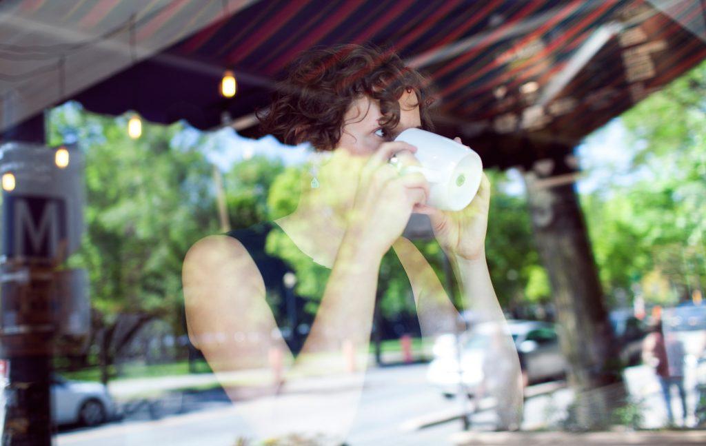 Michelle Darwin, portrait with coffee shop window reflections