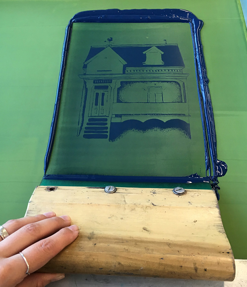 My hand holding a printmaking squeegee on an inked screen showing a Montreal house drawing